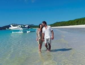 Couple with seaplane on Whitehaven Beach