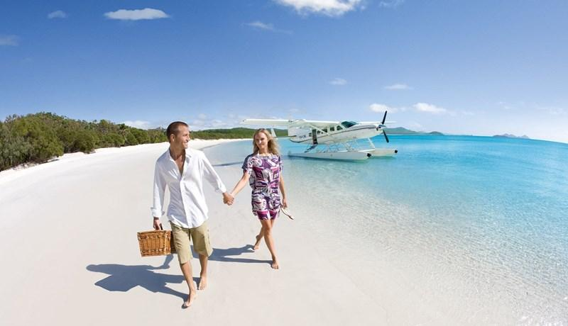couple on whitehaven beach with seaplane in background
