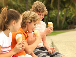 Kids enjoying ice cream on Catseye Beach. Hamilton Island offers great package deals for family summer holidays with kids.