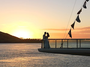 Couple enjoying the beautiful sunset over Hamilton Island from the Yacht Club Flag Deck. Hamilton Island is a much preferred destination for romantic gateways, wedding and honeymoons for Australians