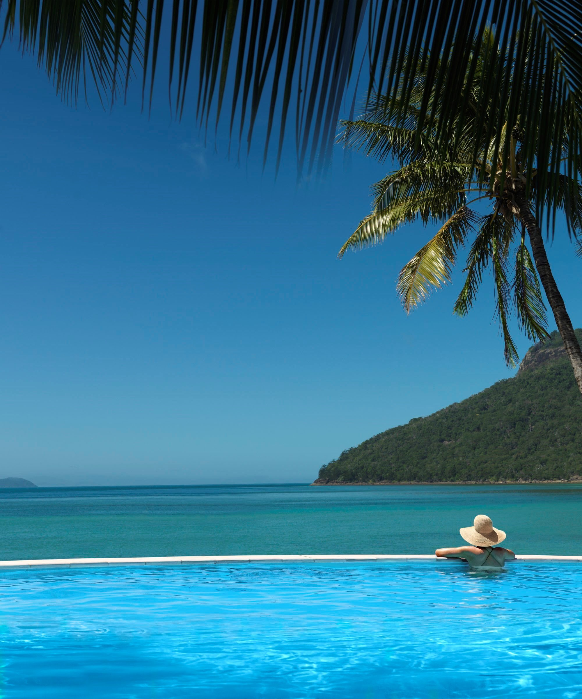 Gorgeous View Of A Woman In Sails Pool Overlooking Catseye Beach. Dream  Destination For A